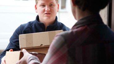 Paktetbote übergibt Paket an Eingangstür